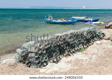 Fish traps drying on the seashore on a background of fishing boats - stock photo