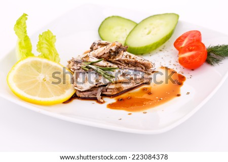 Fish, vegetables and lemon on white plate. - stock photo