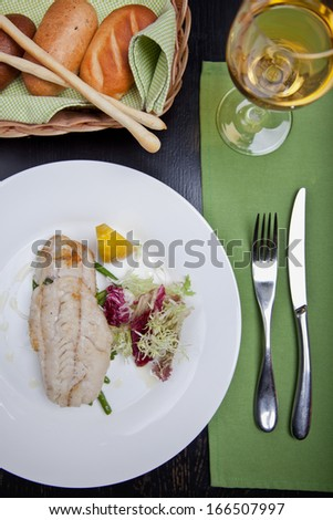 Fish with greens, lemon and asparagus on a plate