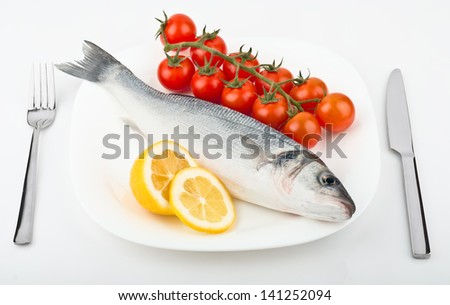 fish with lemon and tomato on plate - stock photo