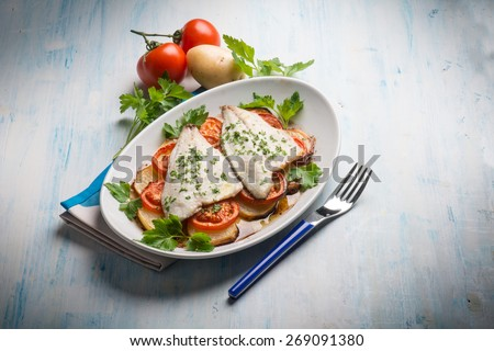 fish with potatoes and tomatoes - stock photo
