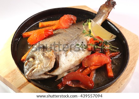 fish with vegetables in hot pan - stock photo