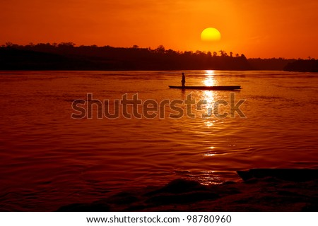 Fisher boat in the river with sunset - stock photo