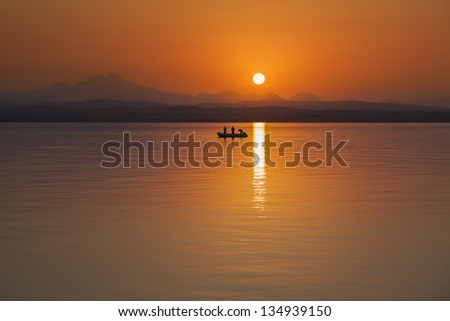 Fisher boat on the ocean during sunset. 3 fishermen on board of the vessel. - stock photo