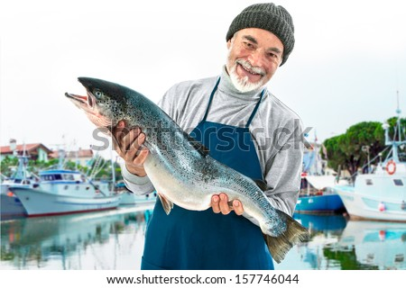 Fisher holding a big atlantic salmon fish in the fishing harbor - stock photo