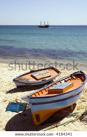 Fisherboat on beach outside Kasbah walls Hammamet Tunisia with old Sailingship in the back - stock photo