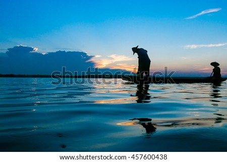 Fisherman action when fishing during sunset - stock photo