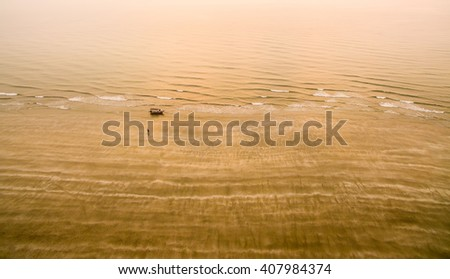 fisherman and boat at beach during golden sunrise - stock photo