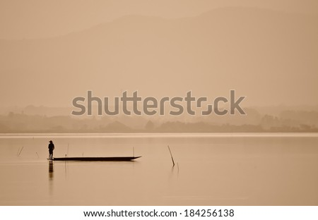 fisherman are standing for fishing in lake in sepia color ; maybe for background