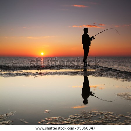 Fisherman at sunrise on the sea - stock photo