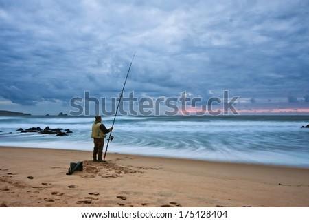 Fisherman at sunset - stock photo