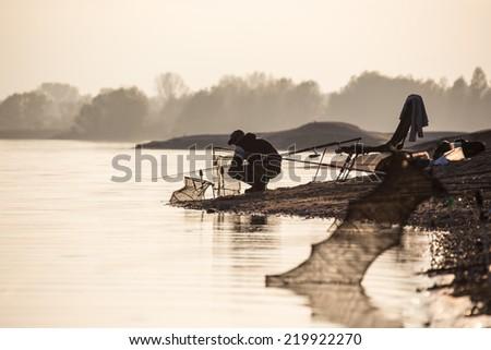 Fisherman at the border of the calm lake - stock photo