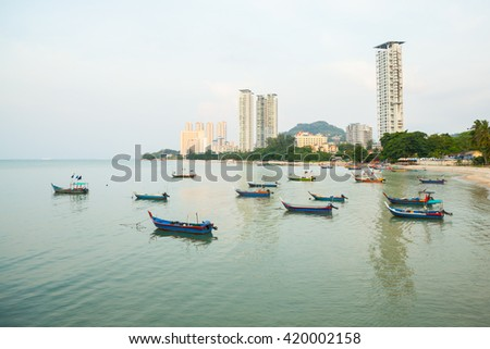 Fisherman beach with Modern Building Architecture at background and Sunset at Tanjung Bungah, Penang, Malaysia.
