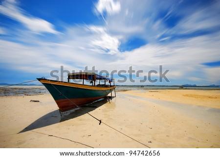 Fisherman boat on low tide shore - stock photo