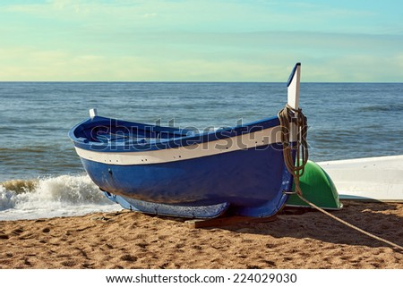 Fisherman boat on the beach at sunrise time            - stock photo