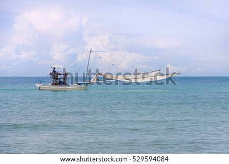 Fisherman boat with seine at sea with beautiful view of nature, clouds on sky