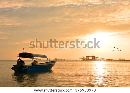 Fisherman boat with sunset background - stock photo