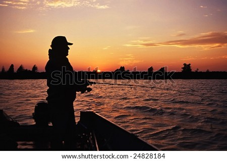 fisherman casting at sunset