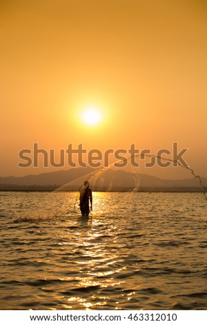 fisherman casting net into the lake