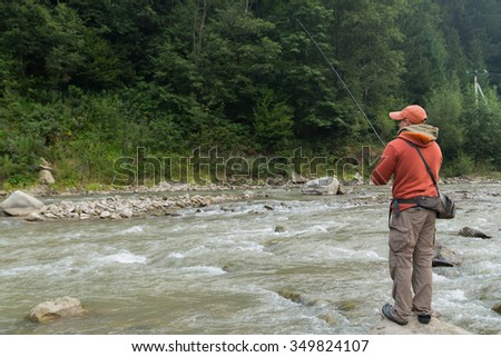 Fisherman catches a trout on a mountain river