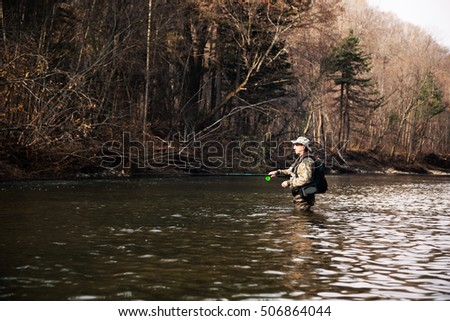 Fisherman catches of grayling in the river with the purest water