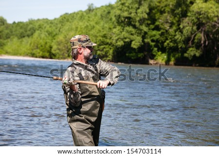 Fisherman catches of salmon in a mountain river. - stock photo
