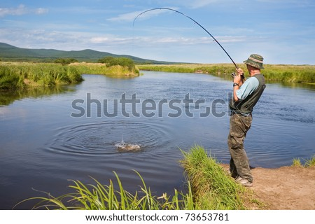 Fisherman catches of salmon (pink salmon) on the river mouth. - stock photo