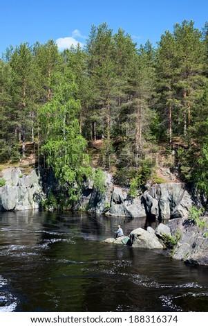 Fisherman catching fish on stream river water - stock photo