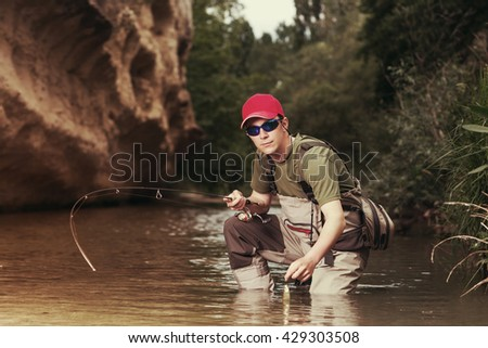 Fisherman caught a fish pulled from the water. Trout fishing on the river. A young man catches a fish in the creek wading.