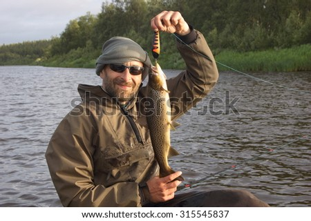 Fisherman caught a nice brown trout. Ponoy river, Kola Peninsula, Russia.