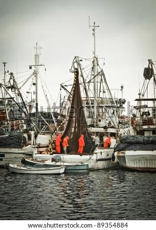 Fisherman crew fixing nets on fishing boat, Zadar, Croatia - stock photo
