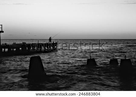 Fisherman figure in the movement on the wharf at dusk. Black and white image. Motion blur. unrecognizable person - stock photo