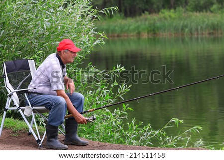Fisherman fishes in the river. Middle aged man. - stock photo