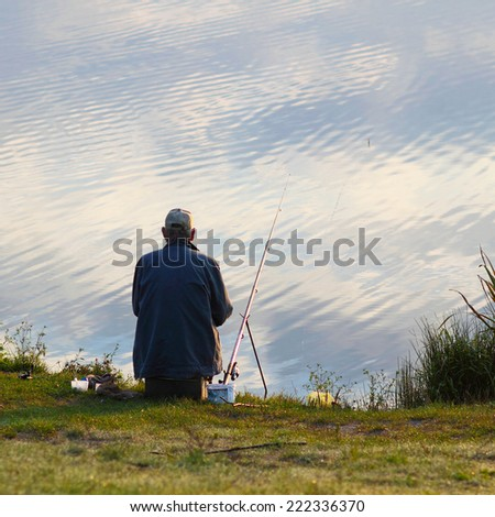 Fisherman fishing. A fisherman catches a fish in the morning - stock photo