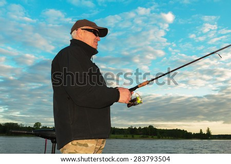 Fisherman fishing at sunset - stock photo