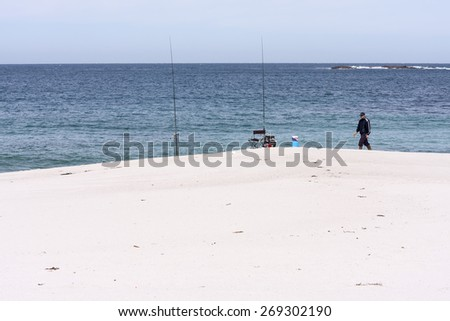 Fisherman fishing from the sand on the beach