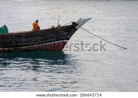 fisherman fishing off a moored dhow boat at anchor against a calm ocean water background - stock photo