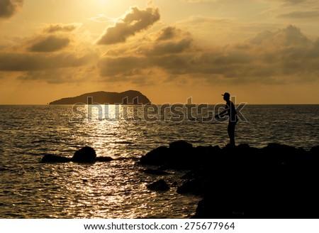 Fisherman fishing silhouette at sunset. - stock photo