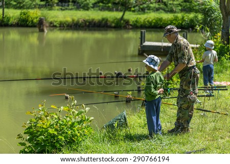 Fisherman fishing with his grandsons - stock photo