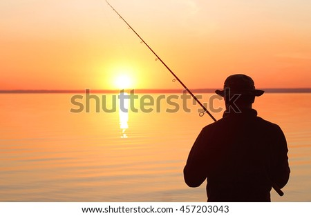 Fisherman fishing with spinning rod on a river bank at sunrise