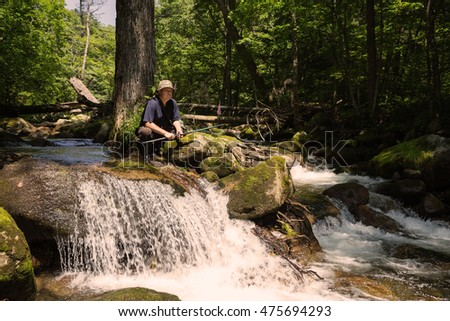 Fisherman has a rest at the mountain river in the wild forest