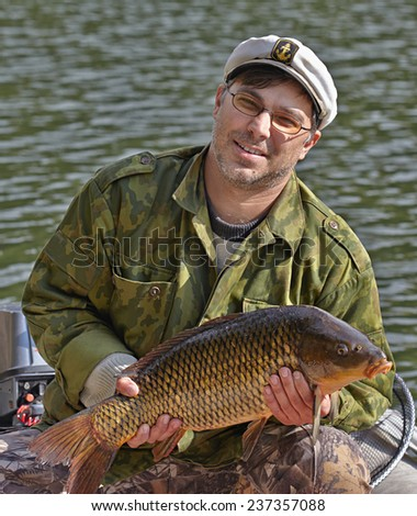 Fisherman holding a fish carp - stock photo