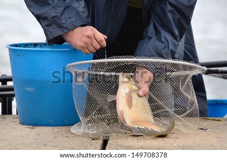 Fisherman holding a fishing net with big bream catching in river - stock photo