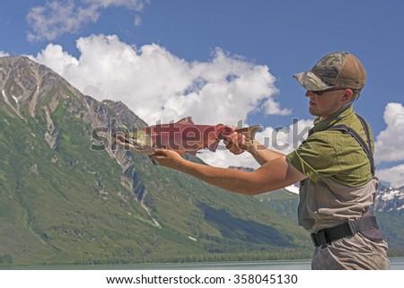 Fisherman Holding a Sockeye Salmon on Crescent Lake in Alaska - stock photo