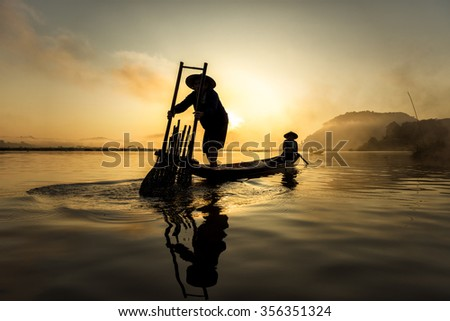 Fisherman in action when fishing in the lake , Thailand - stock photo