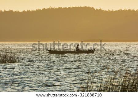 Fisherman in boat at sunrise - stock photo