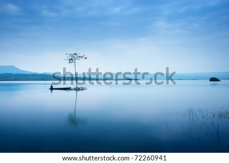 Fisherman in  fishing boat at big lake on the mountain - stock photo
