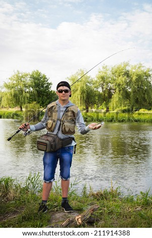 Fisherman in professional gear on the river bank. Fisherman catching fish and holds it in his hand. Pike, fish, fishing, nature, fishing rod - the concept of leisure. Article about fishing. - stock photo