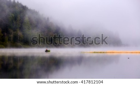 Fisherman in the boat at Lake Cerknica early in the morning. Fog rising above the water. Forest in spring colors reflecting in the calm lake surface.