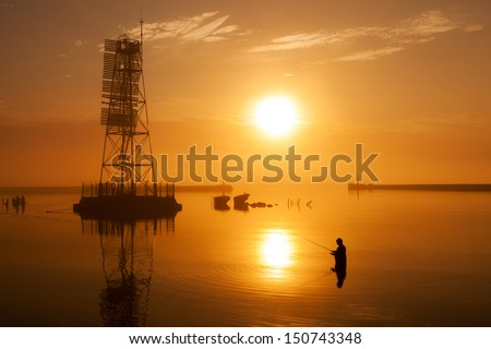 Fisherman in the water near lighthouse on the outstanding sunset background with reflection on foggy weather on Baltic sea - stock photo